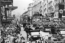 Crowds line a street. In the center, moving a long the road, is a double row of open top cars moving through the street with people standing and sitting in them.