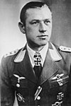A man wearing a military uniform with various military decorations including an Iron Cross displayed at the front of his uniform collar.
