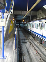 An underground station with two tracks in Madrid. A blue and white subway train is entering the station on the left.