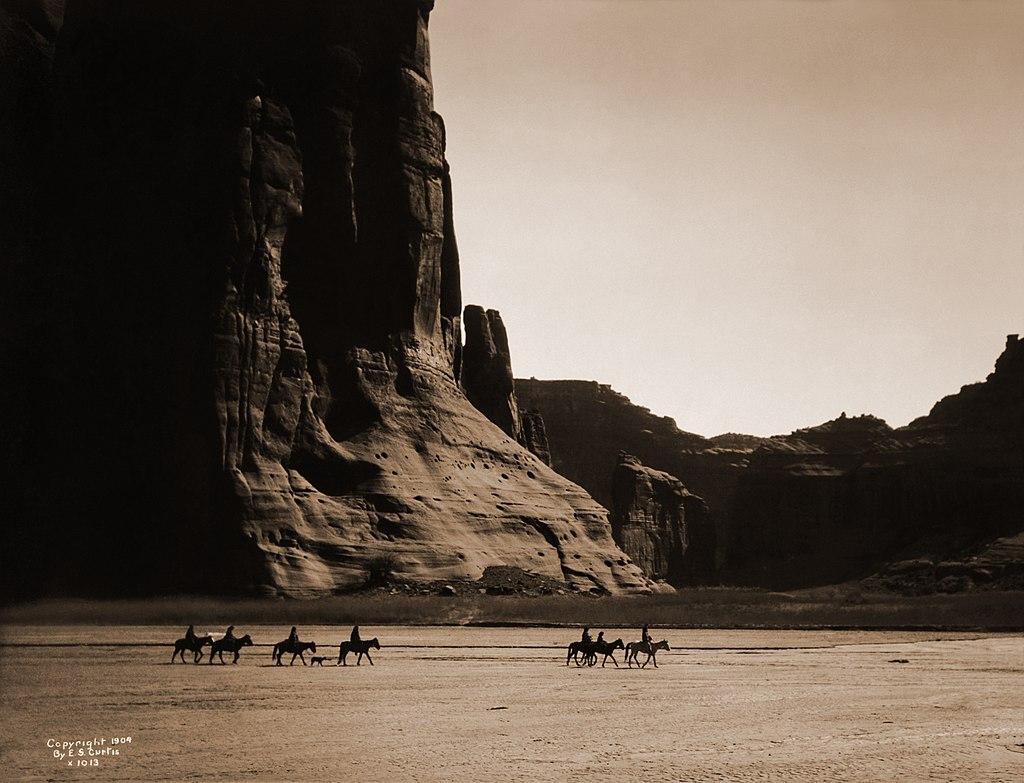 Sept cavaliers et un chien cheminent dans le canyon de Chelly en Arizona, photographie d'Edward Sheriff Curtis prise en 1904.  (définition réelle 3619×2667)