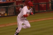 "A dark-skinned man with ""NGEL"" visible in red text on a white jersey runs from home plate to first base. He has on red and black batting gloves, a red batting helmet, white pants and black shinguards."