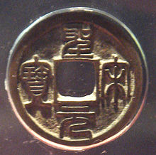 A circular golden coin with a square hole in the center and four Chinese characters, one to each side of the hole, embossed into the body of the coin.