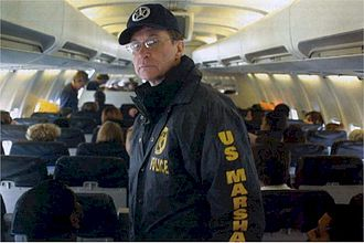 "Justice Prisoner and Alien Transportation System - A U.S. Marshal on a ""Con Air"" flight."