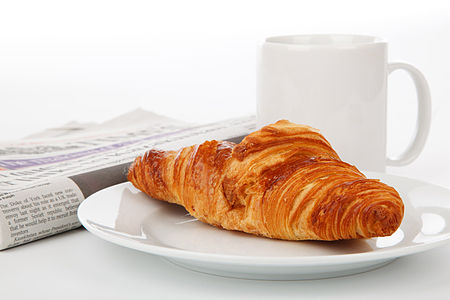A croissant for breakfast, with newspaper