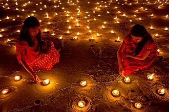 Diwali - Lighting candle and clay lamp in their house and at temples during Diwali night