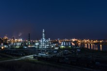 Oil refinery buildings along a waterway at night