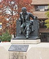 Statue d'un homme assis sur une chaise posée sur un socle de pierre au milieu d'un parc