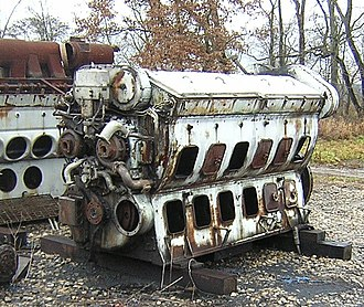 "Diesel locomotive - An EMD 12-567B Roots-blown 12-cylinder diesel engine (square ""hand holes""), stored pending rebuild, and missing some components, most notably the two Roots blowers, with a 16-567C or D 16-cylinder engine (round ""hand holes"")."