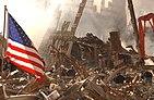 Záchranáři prolézají sutinami a kouřem v místě Světového obchodního centra a vlevo vlaje americká vlajka