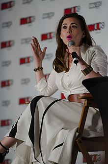Photograph of a brunette white woman sitting on a chair and holding a microphone.
