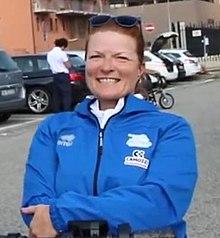 Imagine de cap a unei femei albe într-un kit albastru strălucitor, cu mașini în fundal.