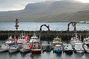 The harbor at Fuglafjørður, Faroe Islands shows seven typical Faroe boats used for fishing.