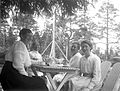 Fyra kvinnor sitter kring ett bord i trädgården och dricker kaffe - Nordiska Museet - NMA.0057513.jpg