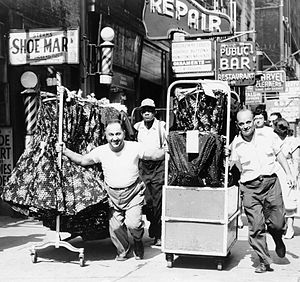 Garment District, Manhattan - Men pulling racks of clothing on busy sidewalk in Garment District in 1955