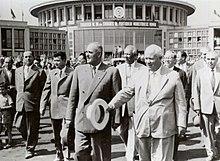 Foto av en gruppe menn i kostyme foran en imponerende sirkulær bygning