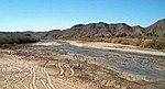 A shallow river with a sandy bed flows through an arid landscape.