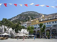 A broad, tree-lined sguare with shops and cafés on the perimeter and tiers of buildings on a slope leading up to the Rock of Gibraltar in the background