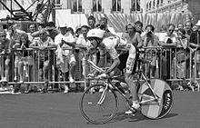 Photographie en noir et blanc, d'un homme porteur d'un casque blanc, roulant sur un vélo