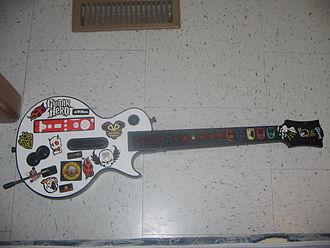 Rhythm game accessories - A Wii Les Paul controller with stickers (included with the controller) applied. The Wii remote can be seen at the top left of the image and has a red silicone skin applied to it.