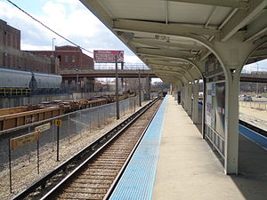 Harlem station (CTA Blue Line Congress branch) - Looking down the platform. The tracks to the left belong to the Baltimore and Ohio Chicago Terminal Railroad with a pair of hopper cars at the Ferrara Candy Company in the background.