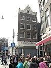 foto van Hoekhuis met gevel onder gebeeldhouwde klokvormige zandstenen top