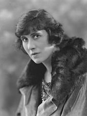 Black and white portrait of a white woman wearing a fur-trimmed coat.