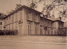 Photographie couleur sépia: un immeuble à deux niveaux sur une parcelle séparée de la rue par un muret muni de grille métallique, nombreuses fenêtres presque toutes obturées par des volets à persiennes, chiens assis dépassant du toit