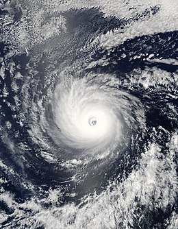 A view of a hurricane over open waters from Space. The hurricane is well-developed, with a symmetric cloud pattern and a well-defined eye at the center.