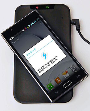 Wireless power transfer - Inductive charging pad for LG smartphone, using the Qi system, an example of near-field wireless transfer.  When the phone is set on the pad, a coil in the pad creates a magnetic field which induces a current in another coil, in the phone, charging its battery.