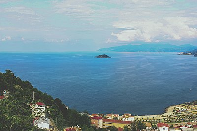 Photograph of the sea from a mountainous coastal city. The camera focuses on a wooded island.