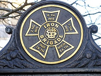 Iron Brigade - Iron Brigade unit badge, a maltese cross design, showing the Wisconsin, Michigan, and Indiana, Union Army regiments, who were the core of the Brigade, on a historical marker, at Gettysburg National Military Park.
