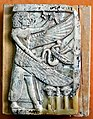 Ivory plaque showing a winged man holding a snake. Nimrud Ivory. Sulaymaniyah Museum.jpg