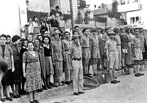 Civil Defence Service - Jewish Civil Defence group in Jerusalem in WWII (then British Mandatory Palestine). The group served as ARP Fire Wardens, equipped with water hoses and buckets, some wearing FW (Fire Watcher) Brodie helmets. Men are in uniform while women wear plain clothes. Composer Josef Tal stands next to the woman with a black sweater.