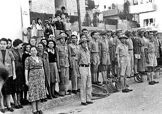 Civil defense - Jewish Civil Defense group in Jerusalem in 1942. The group served as ARP Fire Wardens, equipped with water hoses and buckets, some wearing FW (Fire Watcher) Brodie helmets. Men are in uniform while women wear plain clothes. Composer Josef Tal stands next to the woman with a black sweater.