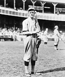 A black-and-white photograph of a man in an old-style white baseball uniform holding a baseball bat over his left shoulder; he is standing on a grass field in a stadium
