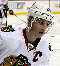 Jonathan Toews in a white away Blackhawks jersey and wearing a white helmet with a clear shield covering his eyes.