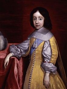 Portrait d'un garçon au cheveux noirs mi-longs portant une sorte de tunique jaune et blanche