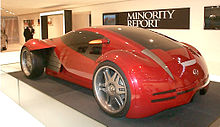 "Futuristic two-door concept car displayed in front of a banner labeled ""Minority Report""."