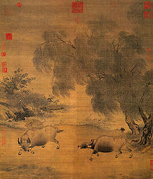 A square painting depicting two oxen fighting against each other at the bank of a river. The ox to the right appears to be trying to turn around to face the ox to the left, while the ox to the left seems to be charging straight at the ox to the right.