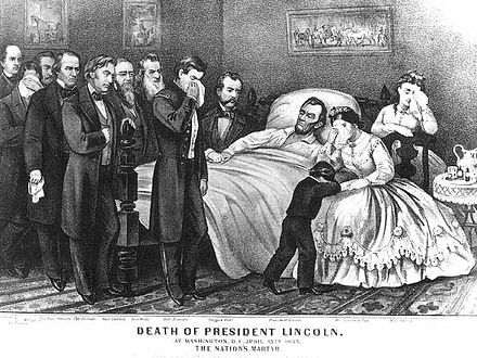 Abraham Lincoln lay on his deathbed at the Petersen House in Washington, surrounded by family, friends and government officials. Lincoln on his deathbed.jpg