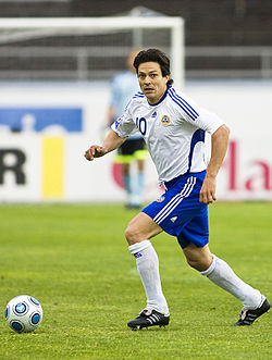 A photograph of a man on a football pitch wearing a white football shirt, blue shorts and white socks. The man is in possession of the football and glancing forward for something or someone out of picture.