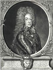 Black and white print of a man wearing armor. He wears an enormous wig of tightly curled hair that flows down to his shoulders and gives him the appearance of having a narrow head.