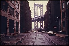 MANHATTAN BRIDGE TOWER IN BROOKLYN, NEW YORK CITY, FRAMED THROUGH NEARBY BUILDINGS. BROOKLYN REMAINS ONE OF AMERICA'S... - NARA - 555898.jpg