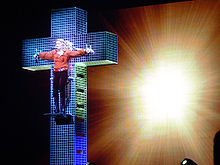 A faraway image showing a blue crystal cross and a blond woman standing on a platform on the cross. The woman is wearing a red shirt and dark brown pants. Her hands are spread apart along the cross's breadth to symbolize as if she has been crucified. Behind the cross, a backdrop is centrally illuminated
