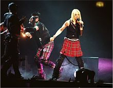 Image of a blond woman wearing a black outfit with a red skirt. She's surrounded by several people wearing gas masks.
