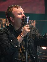 A singer, clothed in a shirt and a dark jacket, is holding a microphone and singing