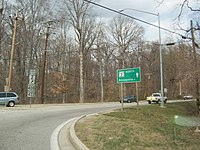 A road at a roundabout in a rural area with a sign to the left reading north Maryland Route 2 upper right arrow Maryland Route 408/Maryland Route 422 and a green sign to the right reading Maryland Route 2 north Annapolis straight
