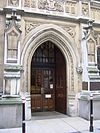 Surrounded by Gothic architecture and enclosed in a pointed arch is a pair of wooden doors, the entrance to the court.