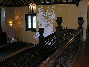 Mayslake Peabody Estate - A hand-carved staircase of walnut leads guests onto the second floor. Architectural damage can be seen on the walls.