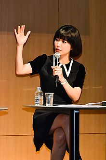 Author Mieko Kawakami seated at a table while speaking into a microphone
